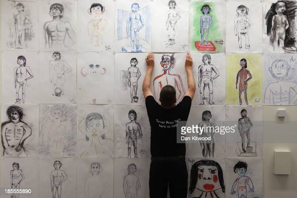 A technician hangs a drawing by a member of the public of Turner Prize nominated artist David Shrigley's 'Life Model' on October 22 2013 in...