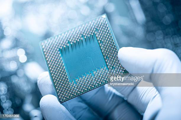Technician holding chip against defocused electronic circuit board