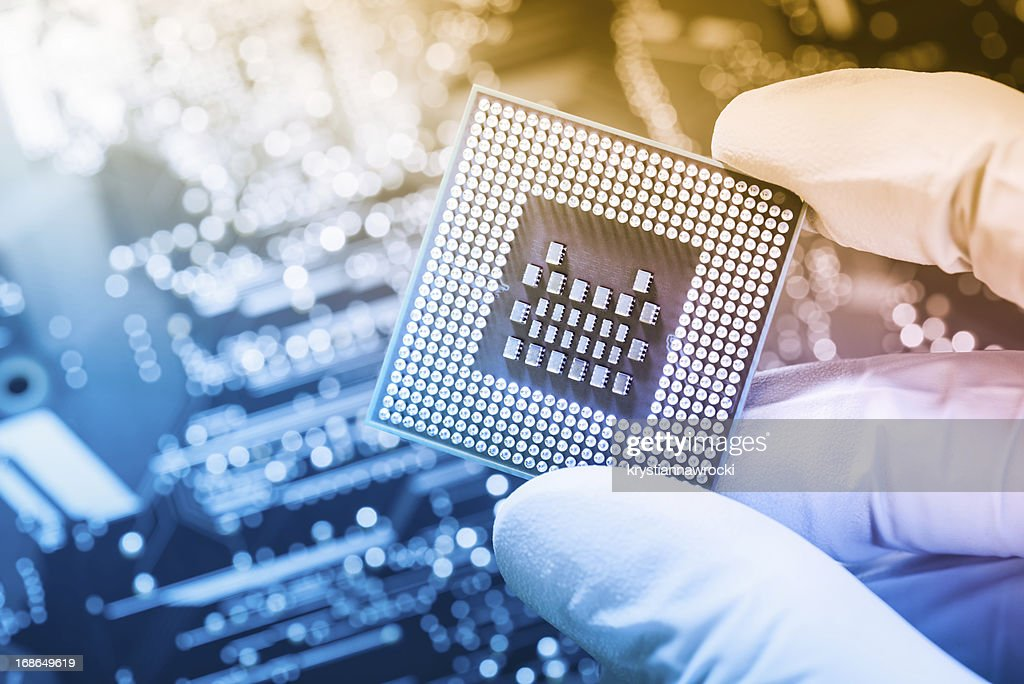 Technician holding chip over defocused circuit board : Stock Photo