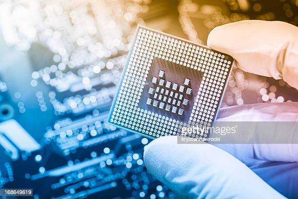 Technician holding chip over defocused circuit board