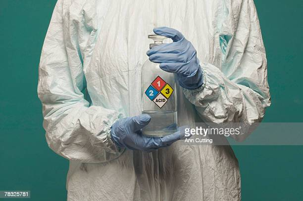 technician holding container of hazardous liquid - acid warning stock photos and pictures
