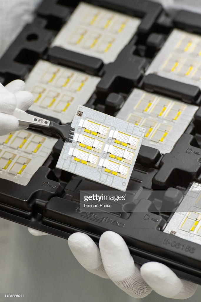 A technician holds a printed circuit board of a high