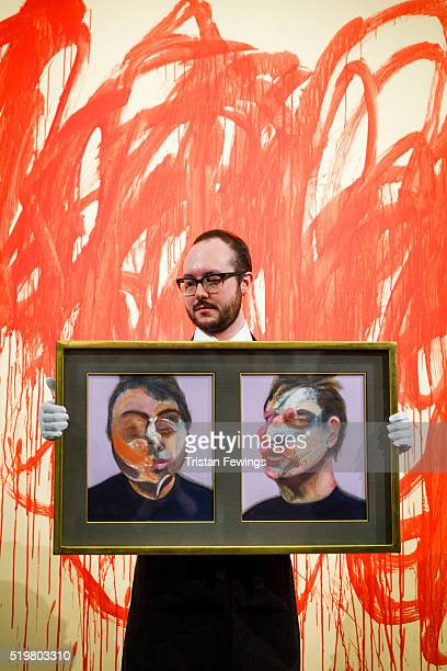 A technician holds Francis Bacon's Two Studies for a SelfPortrait in front of Cy Twombly's Untitled 2004 at Sotheby's on April 8 2016 in London...