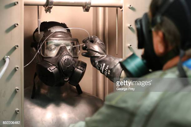 A technician in a gas mask takes measurement readings on the Smartman test dummy at the Smartman Laboratory facility at the US Army's Dugway Proving...