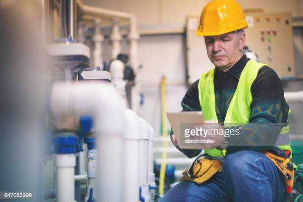 Technician in boiler room using tablet pc