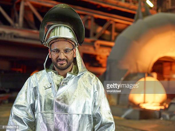A technician in front of blast furnace in full flame retardant protective equipment