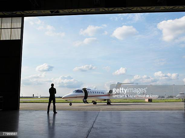 technician in hangar looking at private jet on tarmac. - coathanger stock pictures, royalty-free photos & images