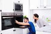 Technician In Overall Fixing Oven In Kitchen