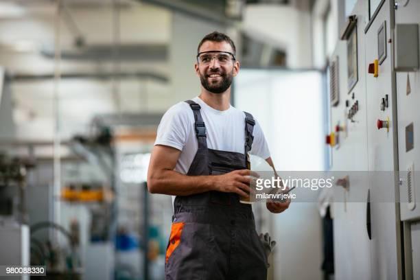 Technician in power substation on coffee break