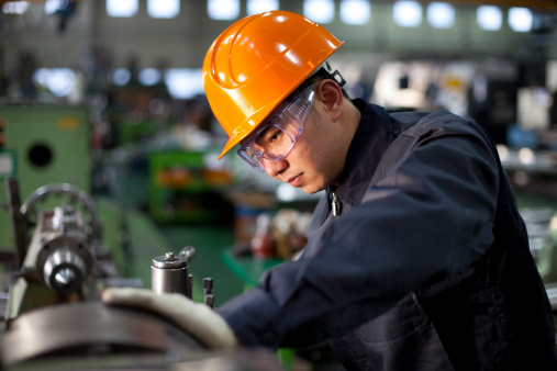 Technician in uniform and hard hat working on a machinery 166091073