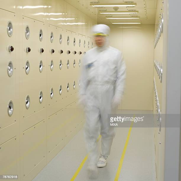 A technician in white lab suit walking in clean room, blurred motion