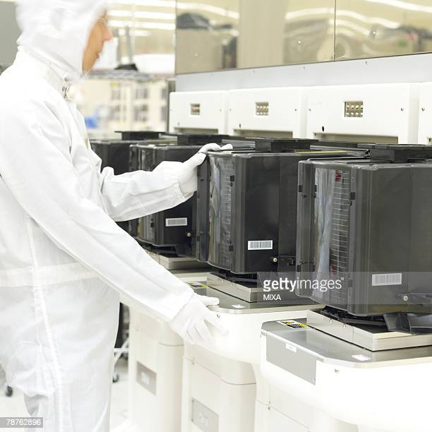 A technician in white lab suit working in laboratory