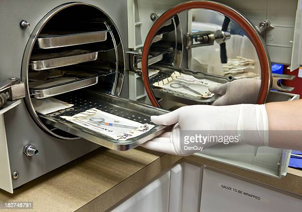 Technician Inserts Surgical Instruments in Autoclave for Sterilization.