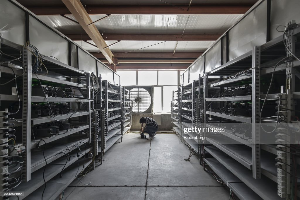 A technician inspects bitcoin mining machines at a mining ...