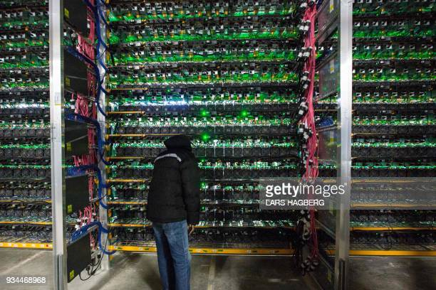 Technician inspects the backside of bitcoin mining at Bitfarms in Saint Hyacinthe, Quebec on March 19, 2018. - Bitcoin is a cryptocurrency and...