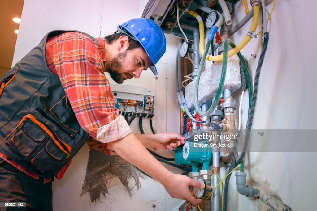 Technician installing heating system : Stock Photo