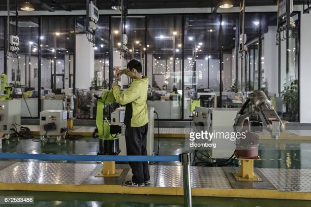 A technician installs a mannequin hand onto an industrial robot at a factory operated by EDeodar Robot Equipment Co a whollyowned subsidiary of...