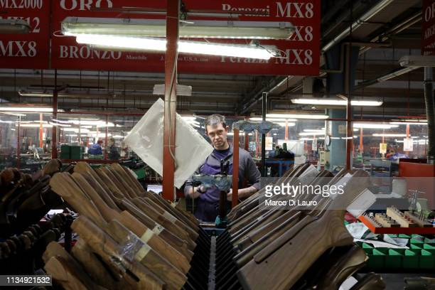 A technician is seen at work near shotgun stocks that are used only to move components and not for sell on April 4 2019 at the Perazzi Armi factory...
