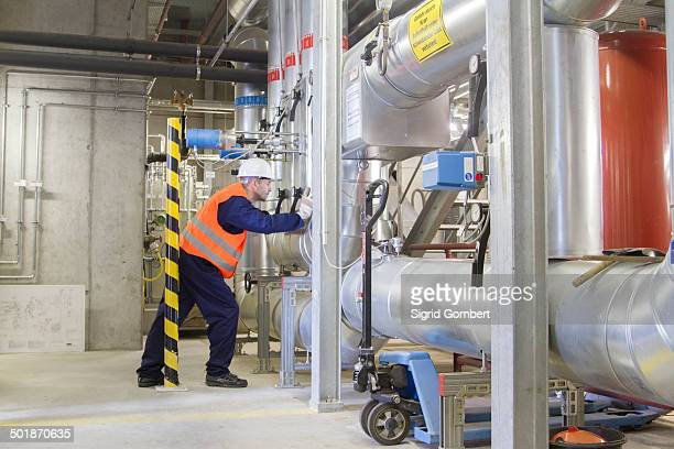 technician leaning forward during check in power station - sigrid gombert stock pictures, royalty-free photos & images