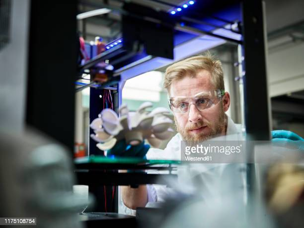 technician looking at turbine wheel being printed in 3d printer - 3d printing stock pictures, royalty-free photos & images