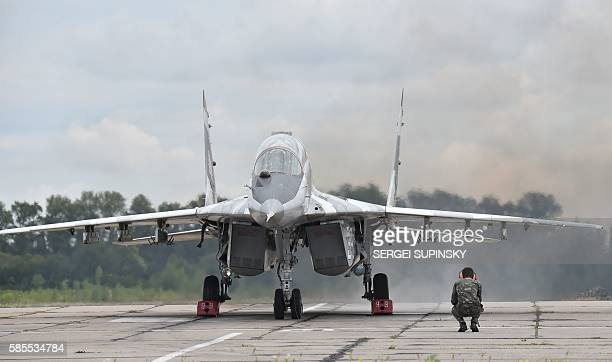 A technician looks at a Ukrainian MIG29 fighter prior its taking off prior to a practical flight during exercises at the Air Force military base in...