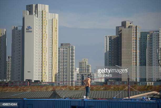 Technician looks towards the skyline of the Songdo area of Incheon outside the weightlifting venue of the 2014 Incheon Asian Games, in Incheon on...