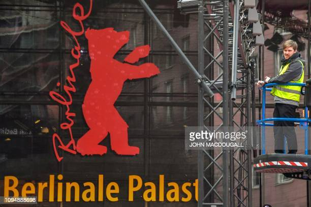 A technician makes some adjustments on the lighting structure in front of the Berlinale Palast on February 7 on the day of the official opening of...