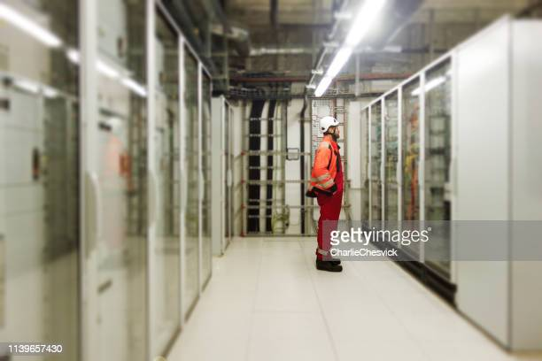 technician making inspection of switchboards, electricity meters and severs in server room - power supply stock pictures, royalty-free photos & images