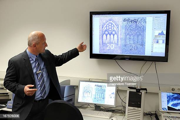 Technician Martin Weber shows the difference between a real and a fake 20 Euro note at the counterfeit money analysis lab of the German Bundesbank...