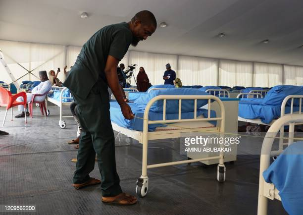 Technician measures the space between beds with a tape at a COVID-19 coronavirus isolation centre at the Sani Abacha stadium in Kano, Nigeria, on...