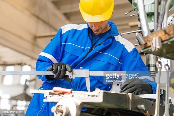 Technician measuring steel bar on drill