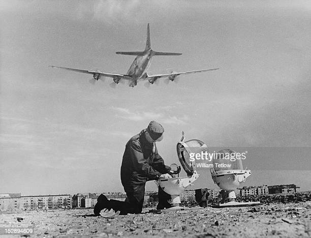 Technician mends the broken glass of a landing light at Tempelhof Airport in Berlin, during the Berlin Airlift, 25th April 1949. A Douglas C-54...