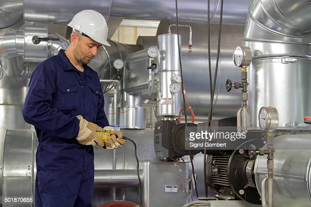 technician monitoring pipe wiring in power station - sigrid gombert stock pictures, royalty-free photos & images
