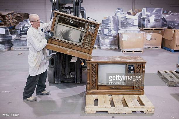A technician moves a wood panel television off a forklift for processing at the ADL Process Inc facility in Toronto Ontario Canada on Monday May 2...