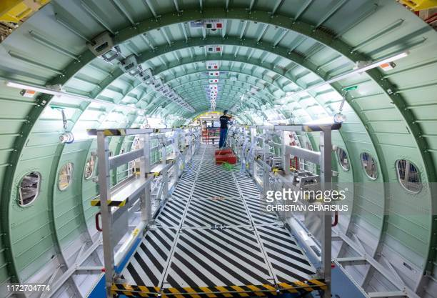 Technician of Airbus works in a fuselage segment of a plane belonging to the Airbus A320 family at the company's Finkenwerder plant in Hamburg,...