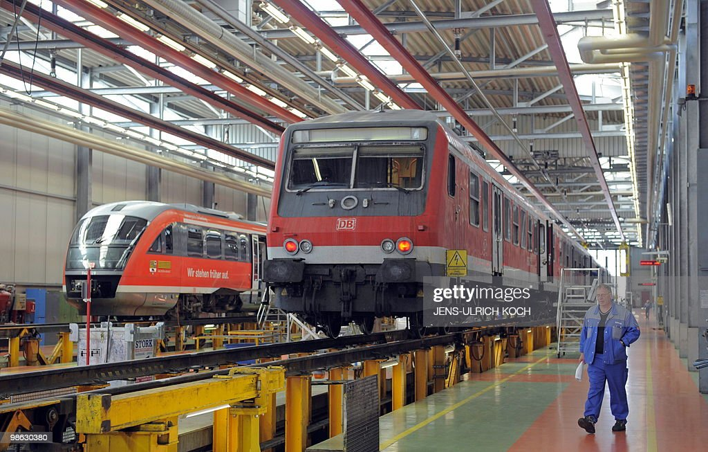 A technician of the DB Regio AG, a subsidiary of Germany's national rail company Deutsche Bahn, walks past railcars in the repair and assembling shop of the Deutsche Bahn in Erfurt, east-central Germany on April 23, 2010.