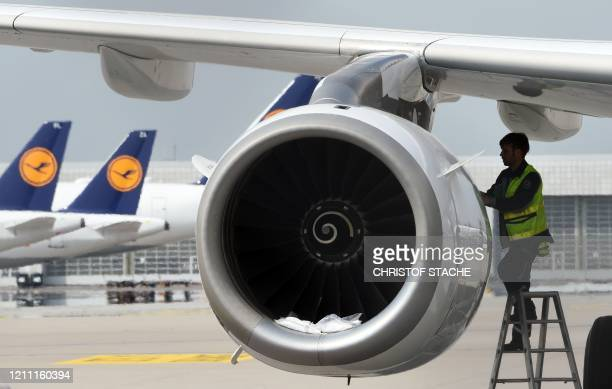 "Technician of the German airline Lufthansa works at a parked plane at the ""Franz-Josef-Strauss"" airport in Munich, southern Germany, on April 28 as..."