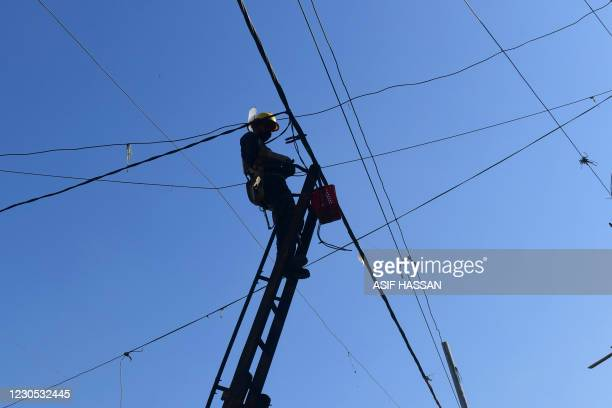Technician of the private power K-Electric company repairs an electric line at a residential area a day after the country's power blackout in the...