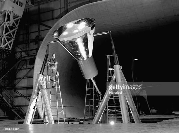 A technician on a ladder examines a Mercury capsule before it is tested in Langley's 30 by 60Foot Wind Tunnel Much of the early work on the Mercury...