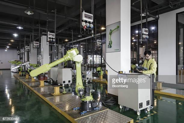 A technician operates a controller on the testing line of a factory operated by EDeodar Robot Equipment Co a whollyowned subsidiary of Ningbo...