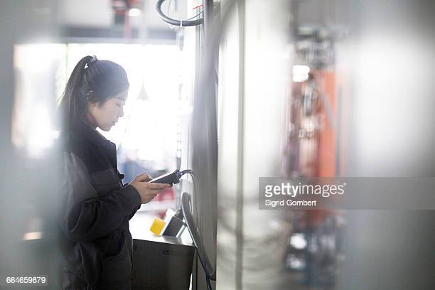 technician operating machine in factory - sigrid gombert stock pictures, royalty-free photos & images