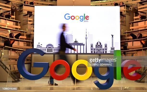 A technician passes by a logo of US internet search giant Google during the opening day of a new Berlin office of Google in Berlin on January 22 2019