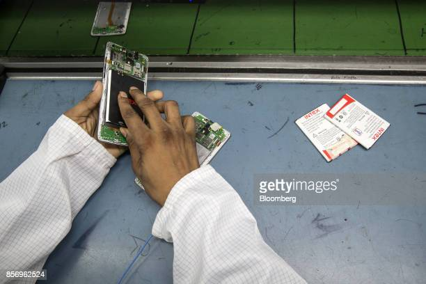 A technician places a battery component on a smartphone on the production line inside the Intex Technologies India Ltd plant in Noida Uttar Pradesh...