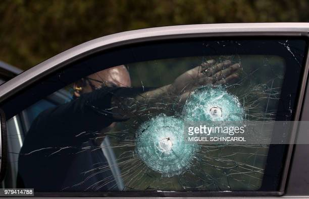 A technician points at the shot of a 357 Magnum at the window of an armoured car at a company in Maua Sao Paulo Brazil on December 15 2017 The city...