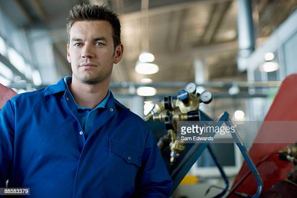 Technician posing in auto shop