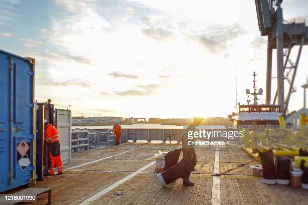 technician pulling equipment on transfer vessel deck and preparing for offshore project in sunrise - nautical vessel stock pictures, royalty-free photos & images