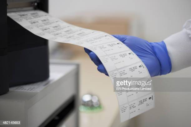 Technician reading printouts in medical laboratory