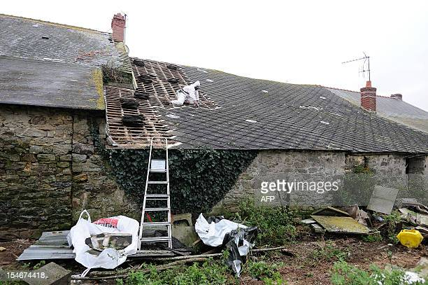 A technician removes asbestos from the roof of a house during its destruction on October 24 in NotreDamedesLandes western France during an important...