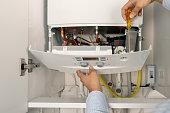 Technician repairing combi Gas Boiler