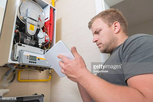 Technician repairing Gas Furnace using digital tablet